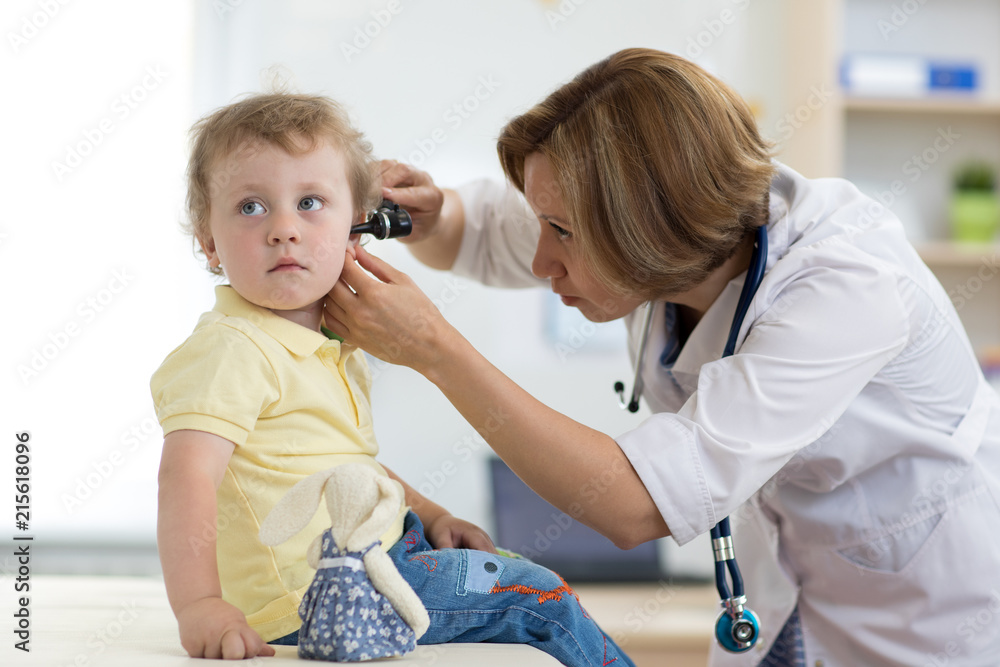 Fototapeta Pediatrician examining child's ears in doctor's office