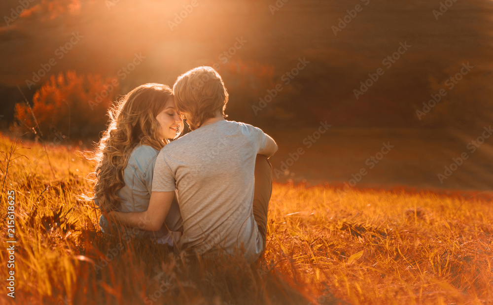 Fototapeta Stylish young couple sitting on a hill and admiring the sunset. A film photo with a light and a sunlight, a foreshortening from the back. Enamored youth in the second before the kiss