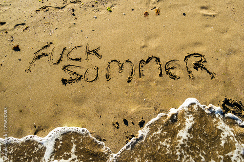 "Stampe  Phrase ""Fuck Summer"" write on the beach sand while a wave arrives during a sunny day"
