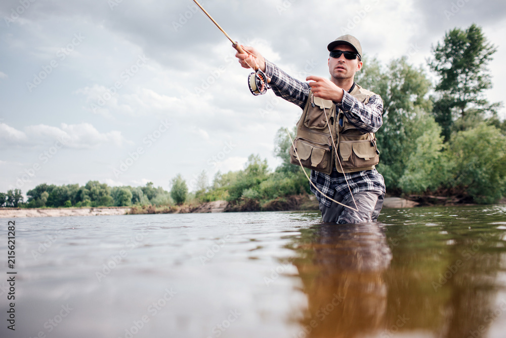 Fototapety, obrazy: Fisherman in action. Guy is throwing spoon of fly rod in water and holding part of it in hand. He looks straight forward. Man wears special protection clothes.