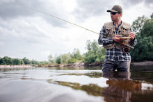Cool Fisherman Stands In Water And Looks Straight Forward. He Is Serious. Guy Holds Fly Rod And Wooden Box Of Artificial Baits And Real Flies In It. He Is Going To Fishing.