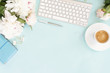 canvas print picture - Flat lay home office workspace background with white modern keyboard, notebook and peony flowers, copy space on blue background