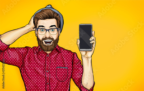 Attractive smiling hipster in specs with phone in the hand in comic style. Pop art man in hat holding smartphone. Digital advertisement male model showing the message or new app on cellphone.
