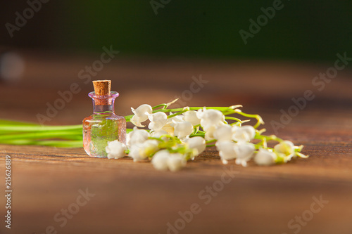 Foto op Plexiglas Lelietje van dalen Essence of flowers on table in beautiful glass jar