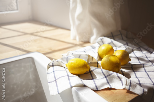 Close up shot of yellow lemons drying on checkered towel in rustic kitchen with sun shining through window. Picture of ripe citrus fruits lying on wooden counter by white sink. Selective focus