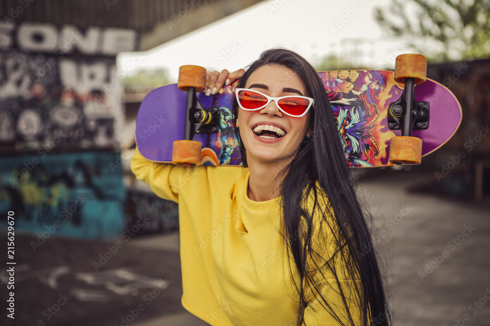 Fototapeta Sexy slim fit brunette woman in sport casual outfit in a skate park. Active leisure on a longboard