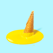 Melted Yellow Fruit Ice Cream In A Waffle Horn On A Light Blue Background. Summer Mood. Creative Concept.