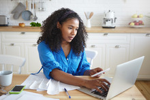 Indoor Shot Of Attractive Serious Young Dark Skinned With Wavy Hair Doing Paperwork In Kitchen, Typing Numbers In Online Form, Holding Paper Bill, Paying For Gas, Electricity And Rent Using Laptop