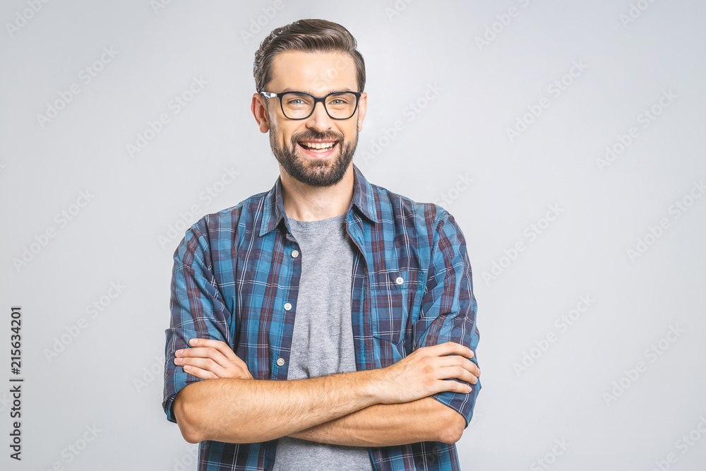 Fototapety, obrazy: Happy young man. Portrait of handsome young man in casual shirt keeping arms crossed and smiling while standing against grey background