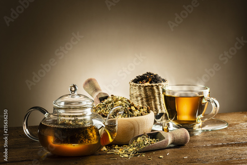glass teapot with steamed cup and herbal tea on wooden table