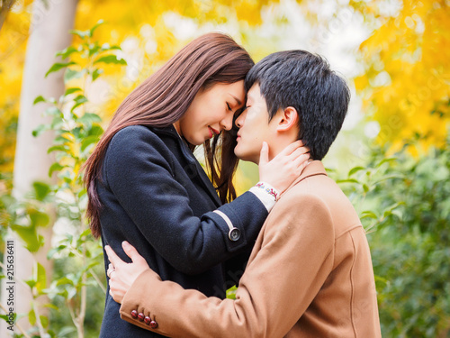 Chinese young man and woman hug and stand together with emotional expression, lover concept Fototapet