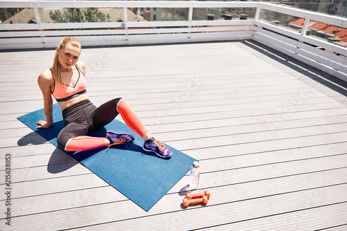 Deurstickers Ontspanning Top view of calm fit lady sitting and relaxing on wide wooden terrace above city. She is training on mat with dumbbells and now having break. Copy space in right side