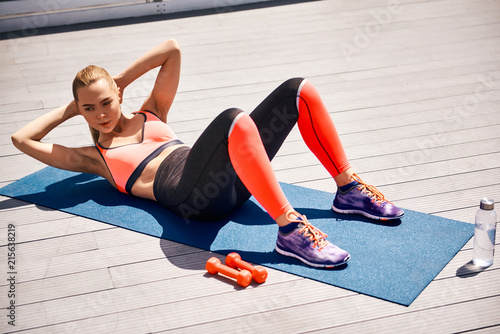 Fotografie, Obraz  Athletic woman is training abdomen in open air