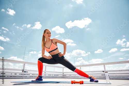 Canvas Print Low angle of slim woman exercising on open terrace under lovely sky