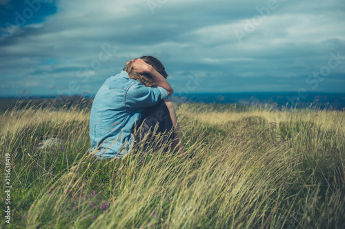 Sad woman in field on windy day Poster