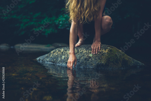 Canvas Print Young woman sitting on rock in a river