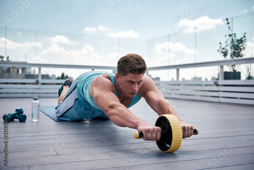 Fotografia  Concentrated young guy is exercising with sport equipment on roof of urban building