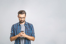 Happy Young Man In Glasses Typing Sms On Gray Background