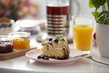 Close-up On Cake On Plate On A Table With Orange Juice During Breakfast. Real Photo