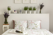Lavender Bedroom Interior With A Bed, Pillows, Wooden Tray With Pot, Flowers And Decorations. Real Photo
