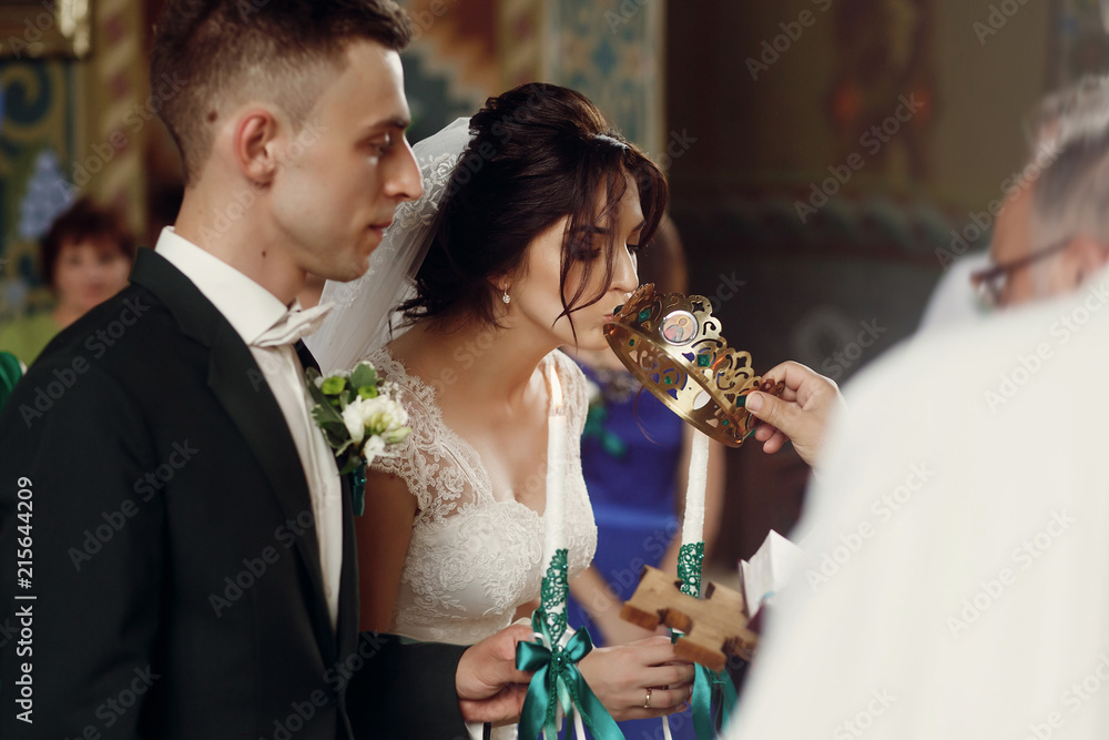 Fototapety, obrazy: Happy spiritual couple, stylish groom and beautiful brunette bride in white dress holding candles at wedding church ceremony during golden crown coronation