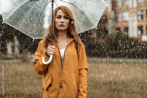 Fotografie, Obraz  Waist up portrait of unhappy girl holding umbrella in hands