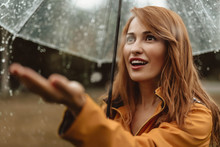 Waist Up Portrait Of Astonished Woman Stretching Hand Under Umbrella And Catching Rain Drops In Delight