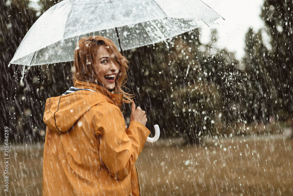 Fototapeta Cheerful pretty girl holding umbrella while strolling outside. She is turning back and looking at camera with true delight and sincere smile. Copy space in right side