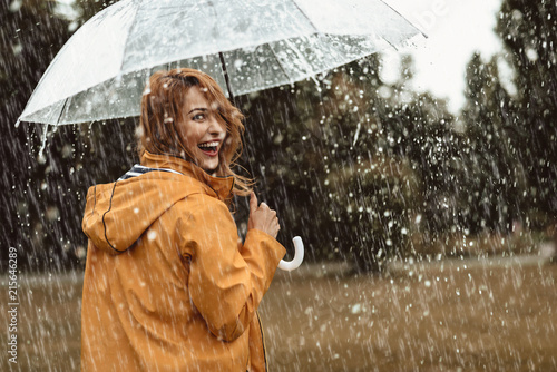 Stampa su Tela Cheerful pretty girl holding umbrella while strolling outside
