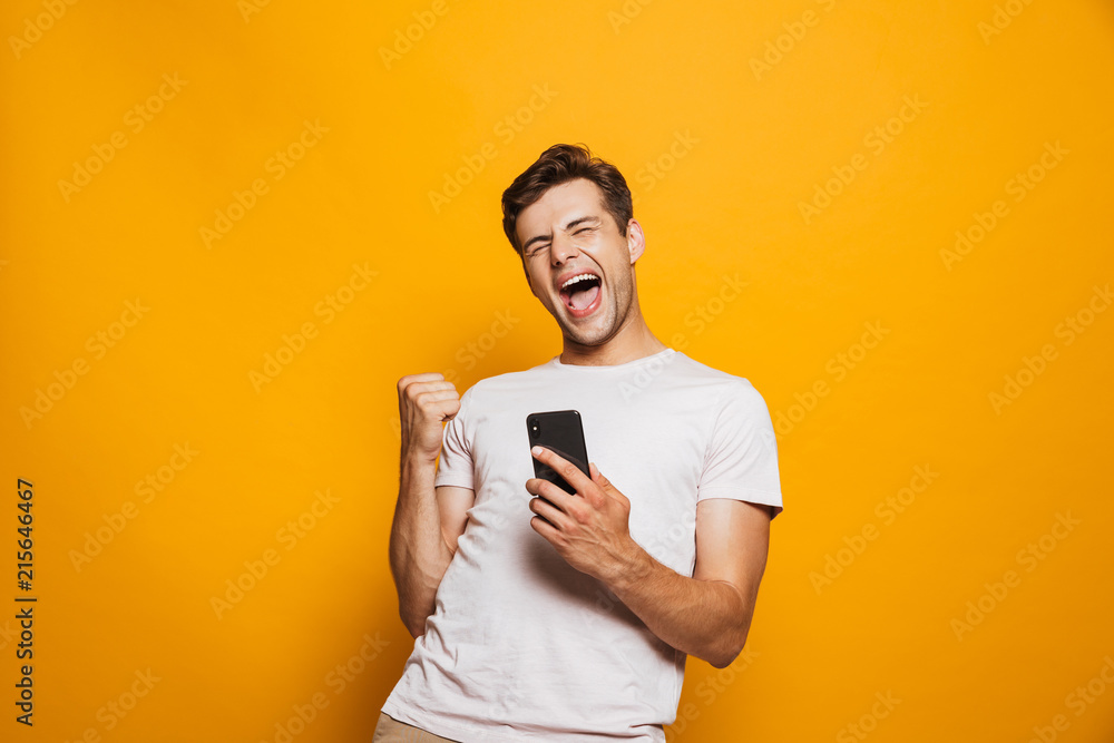 Fototapeta Portrait of a joyful young man holding mobile phone