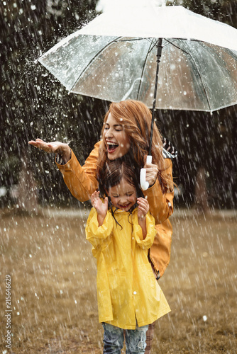 Fotografia Full length of happy mother standing under umbrella with small girl