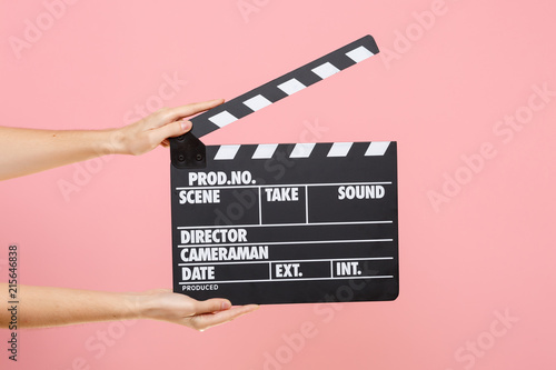 Cuadros en Lienzo Close up female holding in hand classic director clear empty black film making clapperboard isolated on trending pastel pink background