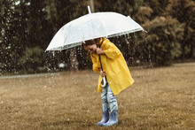Full Length Side View Of Delighted Kid Standing And Holding Umbrella In Hands. She Is Looking Down At Rubber Boots With Great Pleasure And Joy