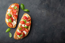 Bruschetta With Tomatoes, Mozzarella Cheese And Basil On A Black Background. Traditional Italian Appetizer Or Snack, Antipasto. Top View With Copy Space. Flat Lay