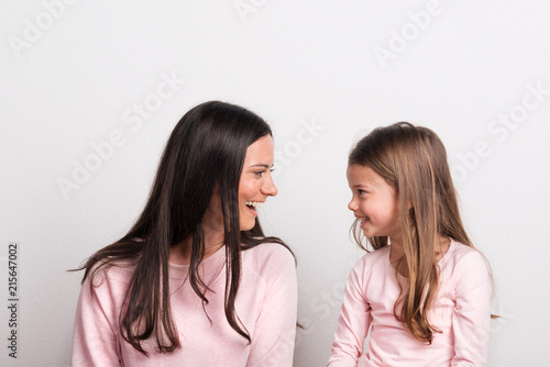 Staande foto Hoogte schaal A small girl and her mother looking at each other in a studio.