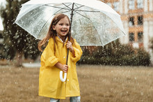 Waist Up Portrait Of Smiling Little Girl Standing On Grass And Holding Umbrella In Hands. She Is Happy And Delighted To Play Outdoors With Raindrops