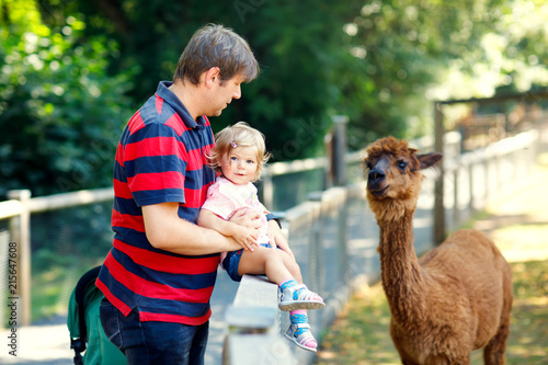 Poster Lama Adorable cute toddler girl and young father feeding lama on a kids farm. Beautiful baby child petting animals in the zoo. man and daughter together