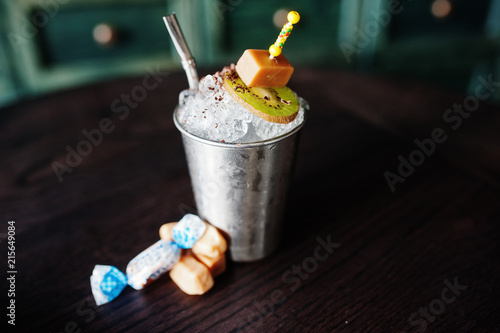 Staande foto Cocktail Alcoholic cocktail with sweets and candies in small silver bucket at bar table.