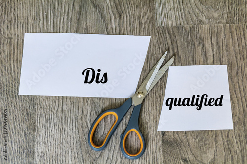 Photo Change of Disqualified to Qualified with Scissors on a Wooden Background