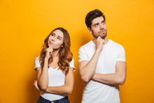 Image Of Happy Young People Man And Woman In Basic Clothing Thinking And Touching Chin While Looking Aside, Isolated Over Yellow Background