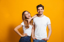 Photo Of Beautiful Couple Man And Woman In Basic Clothing Standing Together And Smiling At Camera, Isolated Over Yellow Background