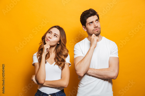 Obraz Image of happy young people man and woman in basic clothing thinking and touching chin while looking aside, isolated over yellow background - fototapety do salonu
