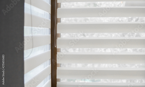 Fotografía  Details of white fabric roller blinds on the plastic window with wood texture in the living room