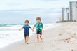 Two little kids boys running on the beach of ocean