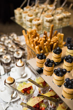 Close-up Of Dessert Table With A Variety Of Platters, With Blueberry Tarts, Puddings And Parfaits, At An Event, Canada