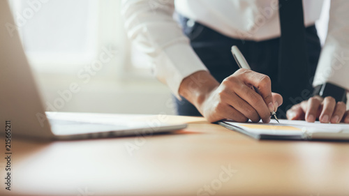 Fotografía  Businessman working at office with sign a document and laptop