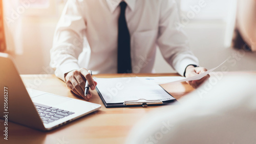man submit resume to employer to review job application. The concept presents the ability for the company to agree with the position of the job.