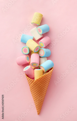 Poster Confiserie Marshmallow candy colorful assortment in an ice cream cone on a pink background viewed from above. Gummy candy variation. Top view