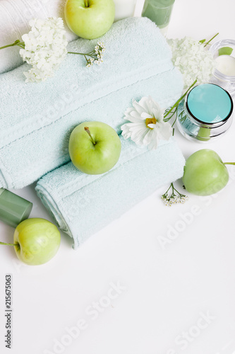 Foto op Aluminium Spa Spa setting on white table. Green apples, towels, cosmos flowers and hydrangeas, cosmetics, candles. Spa resort therapy composition, spa summer concept. Top view