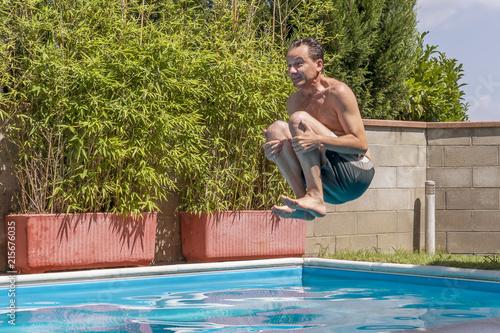 Stampa su Tela Caucasian man takes a bomb dive in the pool